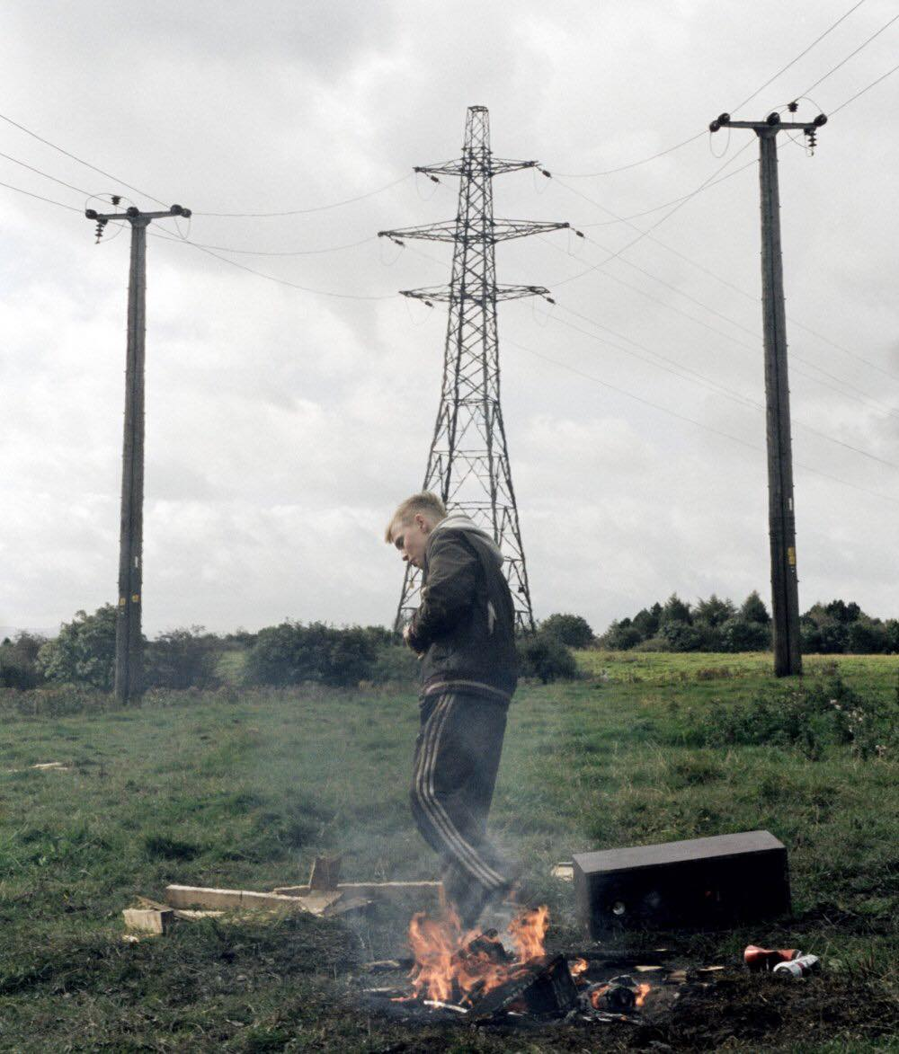 Boy stood wearing a tracksuit in front of a fire on a field, daytime. A large pylon is behind.